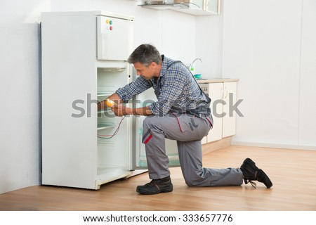 Mature male technician checking fridge with digital multimeter at home