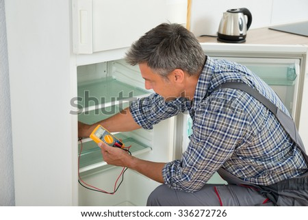 Mature male technician checking fridge with digital multimeter at home - stock photo