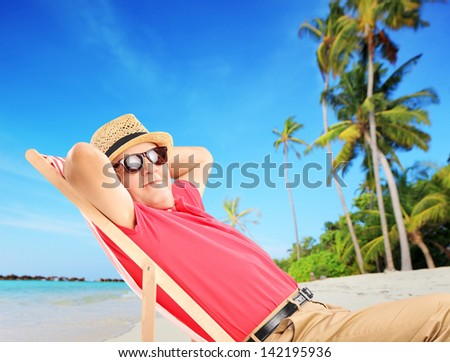 Mature male tourist enjoying on a tropical beach next to a sea and palm trees - stock photo