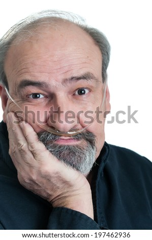 Mature male with a tired, wearied look wearing an Oxygen hose to supplement his O2 - stock photo