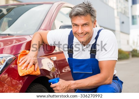 Mature male worker cleaning red car with cloth and spray bottle - stock photo