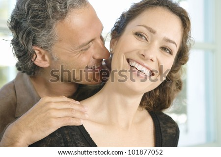 Mature man and woman hugging and whispering in each other's ear at home. - stock photo