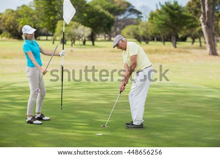 Mature man and woman playing golf while standing on field