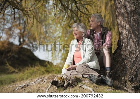 Mature man and woman sitting in the forest