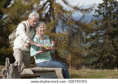 Mature man and woman sitting in the mountains eating fruit