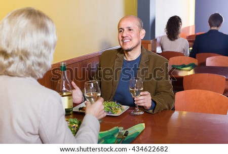 Mature man and woman talking together in restaurant