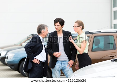 Mature man and young couple standing on a parking place standing in the middle of cars, obviously they are in a sales pitch - stock photo