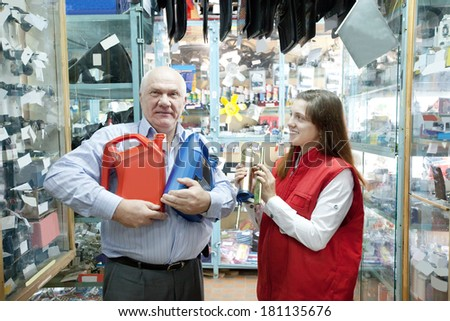 Mature man buys motor oil in auto parts store - stock photo