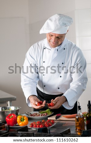 Mature man chef carefully selects cherry tomatoes for dinner preparation at restaurant - stock photo