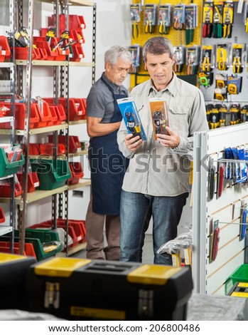 Mature man choosing soldering iron with worker working in background at hardware store