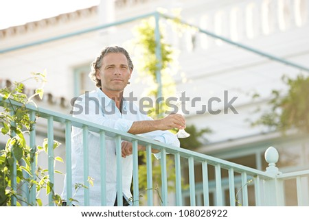Mature man drinking champagne whilst leaning on a balcony.