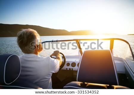 mature man driving speedboat - stock photo