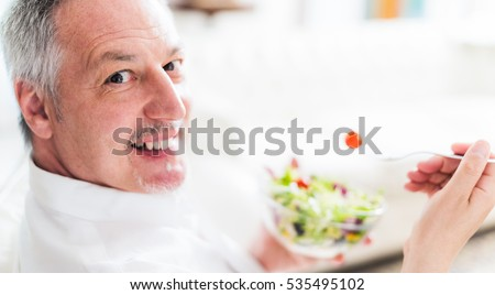 Mature man eating a salad
