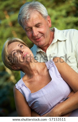 Mature man embracing his partner; - stock photo