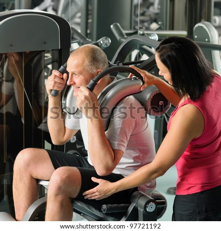 Mature man exercising at gym under supervision of personal trainer - stock photo