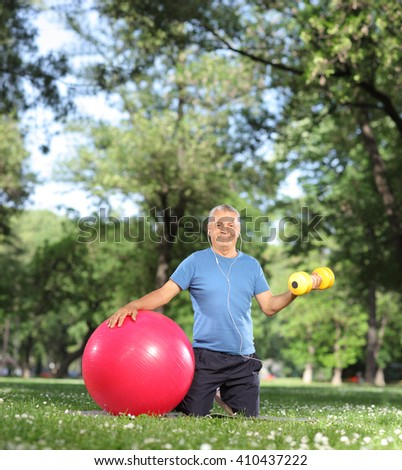 Mature man exercising in park with a yellow dumbbell and a fitness ball shot with tilt and shift lens - stock photo