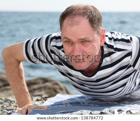 Mature man exercising on a beach - stock photo