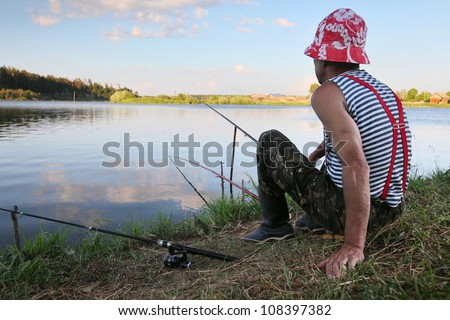 Mature man fishing on a rural pond's coast - stock photo
