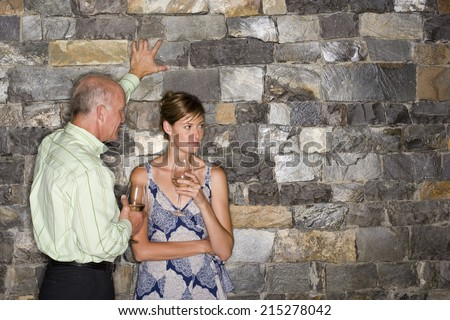 Mature man flirting with younger woman beside stone wall, holding glasses of white wine, woman looking away - stock photo