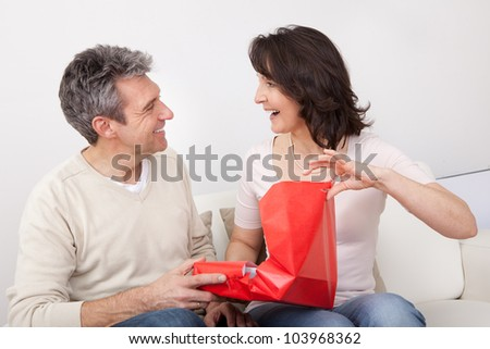 Mature man giving a present to his woman at home - stock photo