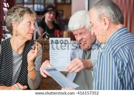 Mature man has difficulty reading menu in a cafe - stock photo