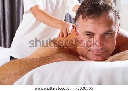 mature man having massage at spa salon - stock photo