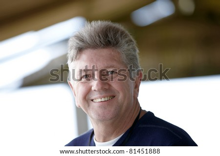 Mature man head and shoulder portrait smiling at the camera - stock photo