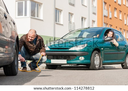 Mature man helping woman with her car breakdown broken problem - stock photo