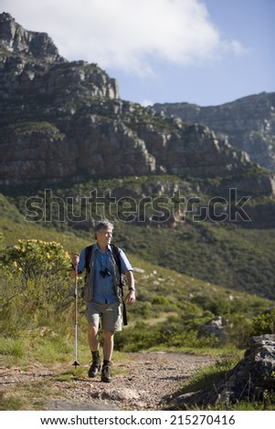 Mature man hiking on mountain trail, carrying rucksack, using hiking pole, looking at scenery, front view - stock photo