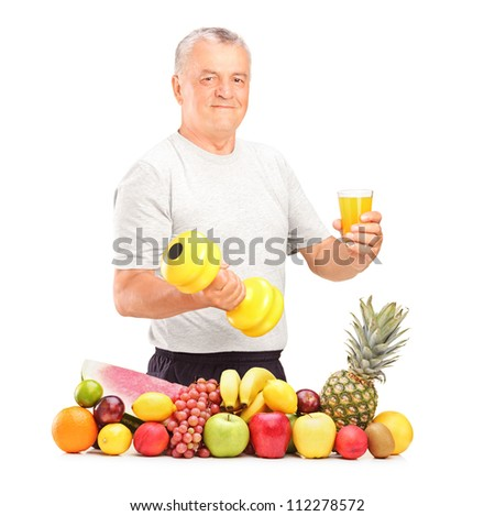 Mature man holding a dumbbell and glass of juice with pile of fruits and vegetables isolated on white - stock photo