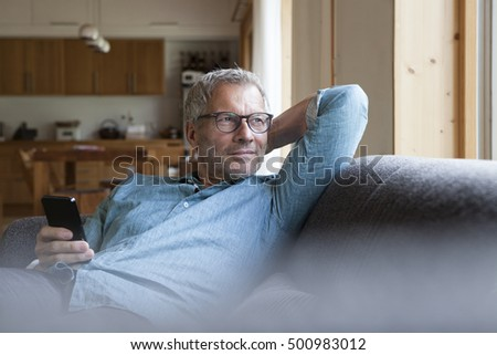 Mature man holding cell phone sitting on couch