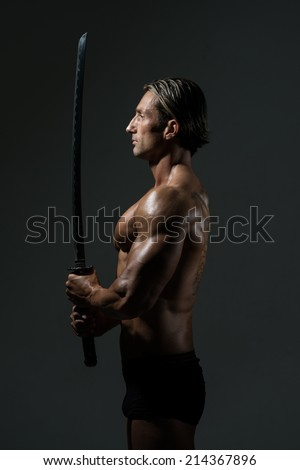 Mature Man In Action With Sword - Portrait Of A Handsome Muscular Ancient Warrior With A Sword - stock photo