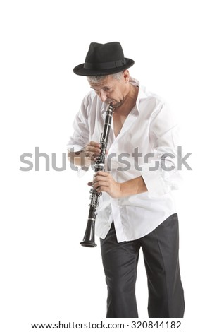 mature man in hat playing clarinet on white studio backround