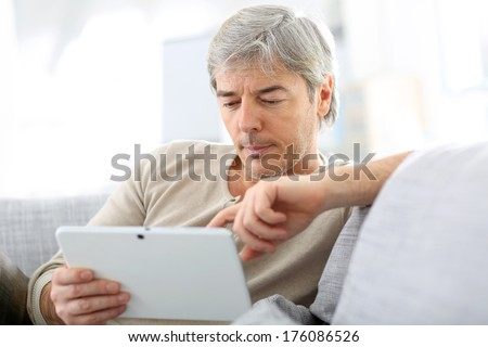 Mature man in sofa websurfing with tablet - stock photo