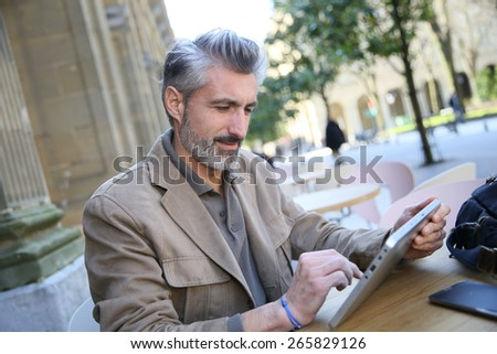 Mature man in town using tablet at coffee shop