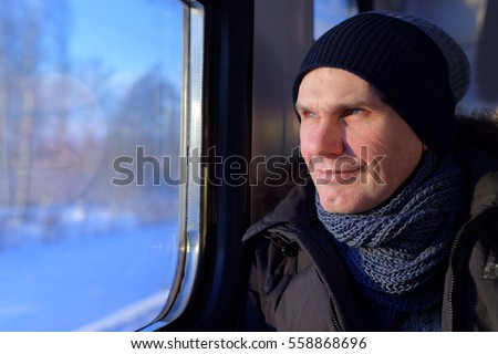 Mature man in winter clothes looks through the window in the commuter train