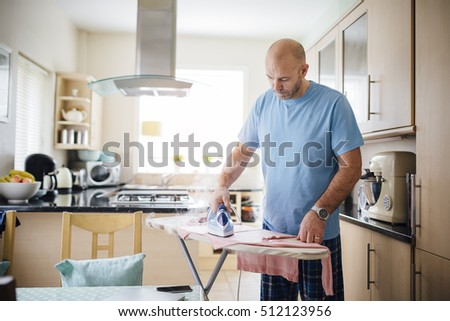 Mature man ironing laundry in the kitchen.