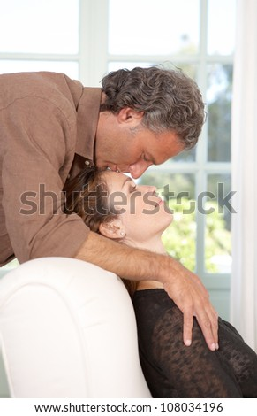 Mature man kissing woman's forehead while lounging at home's living room.