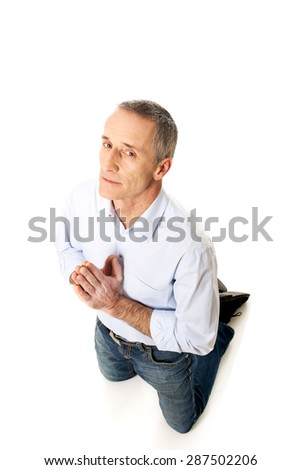 Mature man kneeling and praying to God. - stock photo