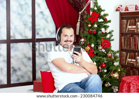 Mature man listening to music on headphones in casual wear  near a New Year tree in home interior . - stock photo