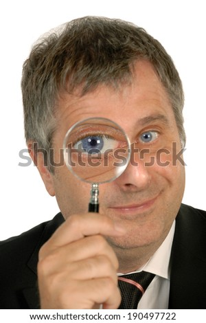 Mature man looking through a magnifier. - stock photo