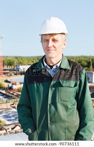 Mature man manual worker in white hardhat near sewage treatment basin - stock photo