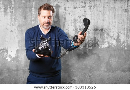 mature man offering a telephone - stock photo