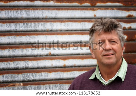 Mature man portrait with a rusty tin background - stock photo