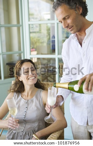 Mature man pouring champagne into flute glasses with partner at home.