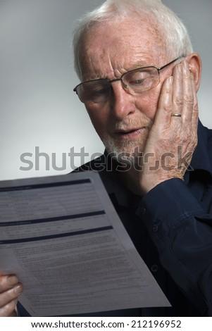 Mature man reading bill - stock photo