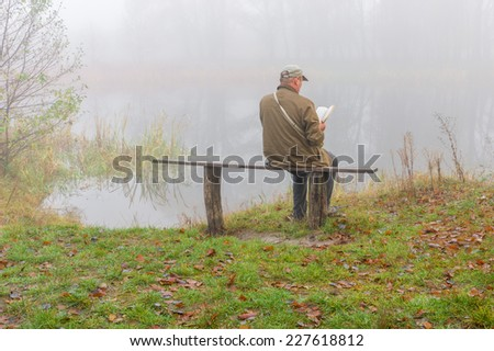 Mature man reading on the river-bank