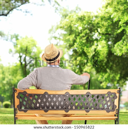 Mature man resting on a wooden bench in park, shot with a tilt and shift lens - stock photo