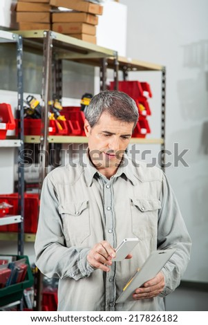 Mature man scanning product through smartphone in hardware store - stock photo