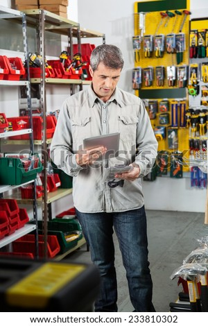 Mature man scanning product through tablet computer in hardware store - stock photo